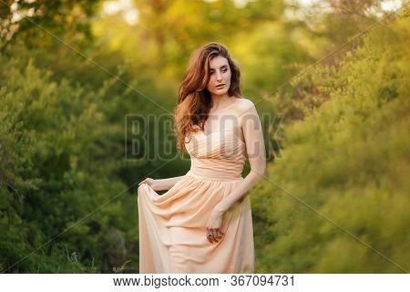 Beauty Romantic Girl Outdoors Enjoying Nature. Beautiful Redhead Model With Waving Glow Hair. Warm T