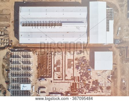 Industrial Buildings Under Construction And Building Materials Warehouse Top Down Aerial View
