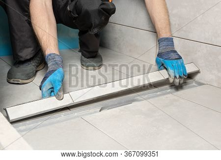A Worker Is Installing A Drain Lid Decorated With Ceramic Tiles In The Bathroom.
