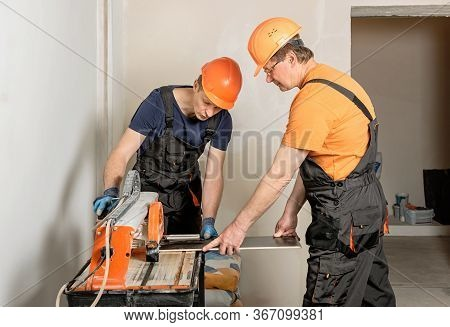 The Workers Are Cutting A Ceramic Tile On A Wet Cutter Saw  Machine.