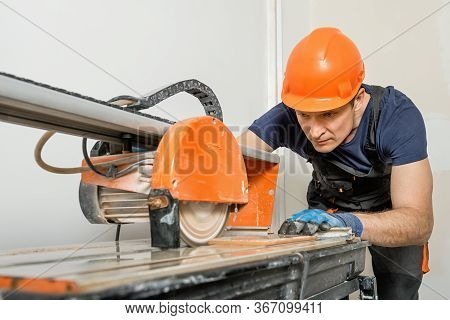 The Worker Is Cutting A Ceramic Tile On A Wet Cutter Saw  Machine.