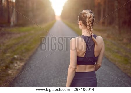 Sporty Healthy Young Woman Walking At Sunrise Along A Rural Road Through A Dense Forest Towards The