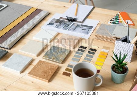 Collections of marble tiles, wallpapers, color swatches, photos of home interior, cup of tea, set of notepapers and domestic plant on desk