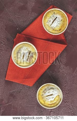 Three Apple Pies In Ceramic Baking Molds With Napkin Ramekin On Dark Red Concrete Table. Top View, F
