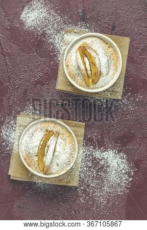 Two Apple Pies In Ceramic Baking Molds Ramekin With Parchment  On Dark Red Concrete Table. Top View,