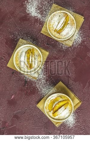 Three Apple Pies In Ceramic Baking Molds Ramekin With Parchment  On Dark Red Concrete Table. Top Vie