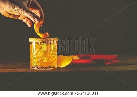 Woman Hand Decorate Orange Twist Alcoholic Cocktail Negroni On Old Wooden Board. Drink With Gin, Cam