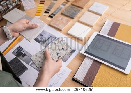 Hands of young female designer holding two samples of marble tile over wooden table with digital tablet, photos of home interior etc