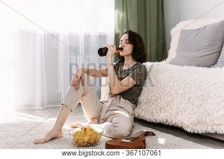 A Young Woman Drinks Beer And Eats Chips At Home. Relax At Home Watching Tv And Movies.