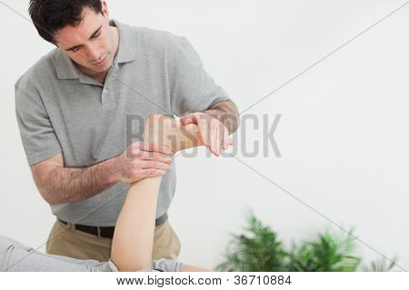 Brown-haired therapist stretching the foot of a patient in a room