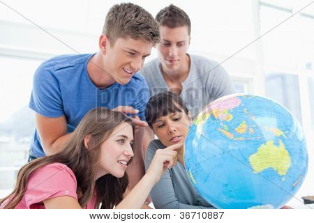 Four smiling students around a globe as two of them point to places in the world