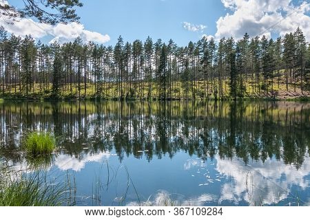 Cloudy Sky And Tree Reflection In Secluded Area By The Lake. Calm Waters And Cloudy Sky. Sweden. Sel