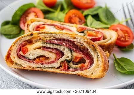 Italian Food Pizza Roll Stromboli With Cheese, Salami, Spinach And Red Pepper A Light Background.