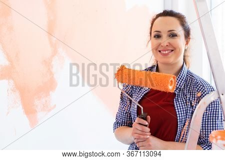 Beautiful Female Painting The Wall With Paint Roller. Portrait Of A Young Beautiful Woman Painting W