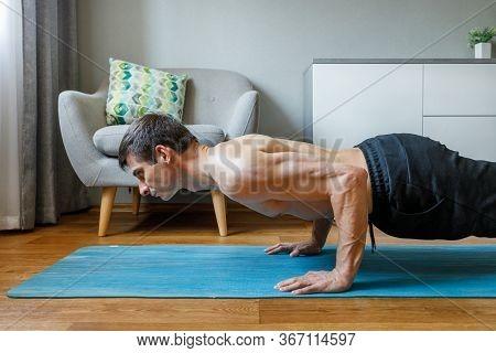 Man In Chaturanga Pose Doing Vinyasa Flow At Home.