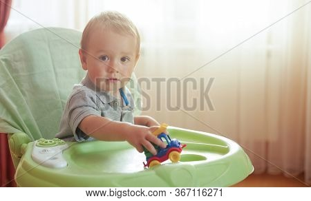 Little Cute Baby Playing With Toy Car Sitting In Highchair Looking At Camera. Cozy Living Room Inter