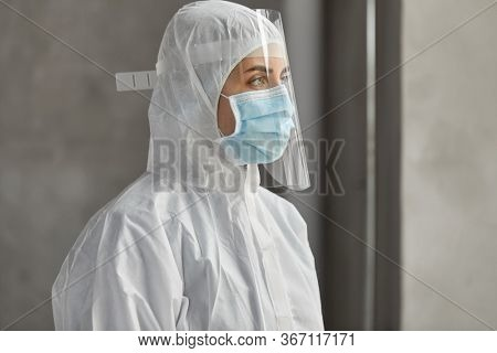 health safety, medicine and pandemic concept - close up of female doctor or scientist in protective wear, medical mask and face shield for protection from virus disease