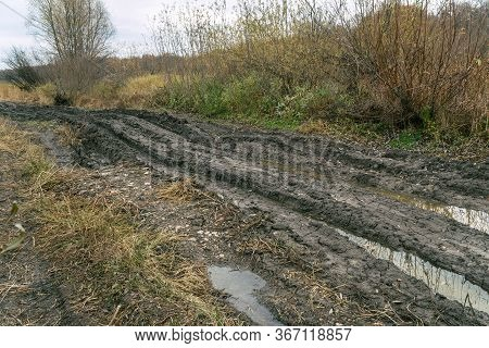 An Impassable Road, Off-road Track In Autumn Forest. Deep Ruts In The Slushy Autumn Road