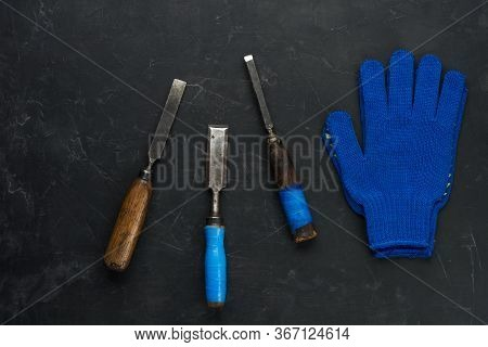 Old Carpenter Tools And Working Gloves On Dark Concrete Background. Minimal Black.