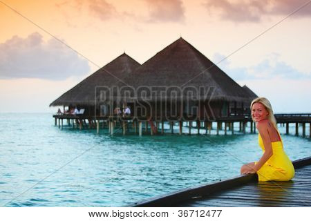 woman on tropical beach house back on the background