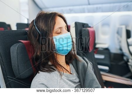 Tired Woman In Virus Protection Face Mask Sleeping In Empty Airplane During Covid-19 Evacuation Flig