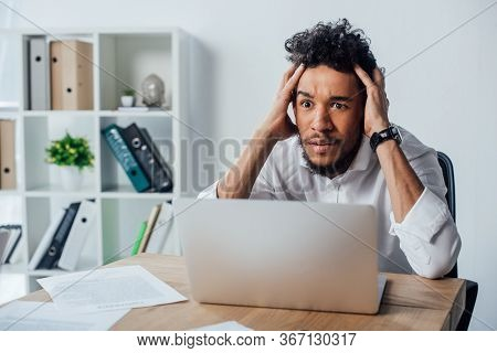 Selective Focus Of Concentrated African American Businessman Sitting Near Laptop And Papers On Table