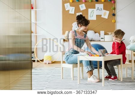 Young Boy At School On Occupational Therapy Classes With Young Psychotherapist