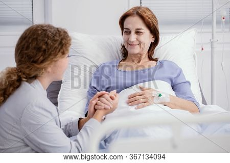 Smiling Elderly Woman And Caring Nurse Holding Her Hand In The Hospice