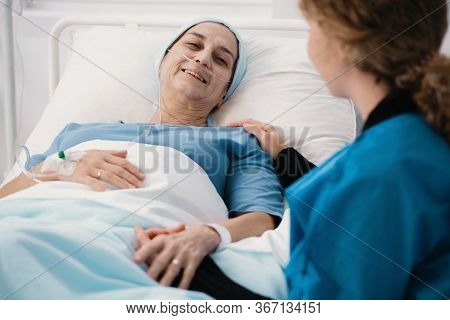 Helpful Caregiver And Positive Woman With Cancer In The Hospice