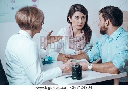 Happy Married Couple With Problem Of Infertility And During Positive Doctor Visit