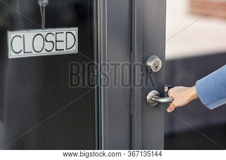 small business, pandemic and service concept - hand trying to open closed office door