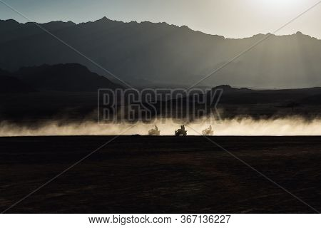 Desert At Sunset. Silhouettes Of People Moving On Buggy Car In A Cloud Of Dust And Sand. Travel Conc