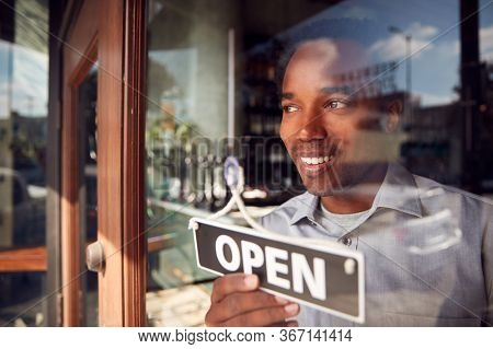 Male Owner Of Start Up Coffee Shop Or Restaurant Turning Round Open Sign On Door