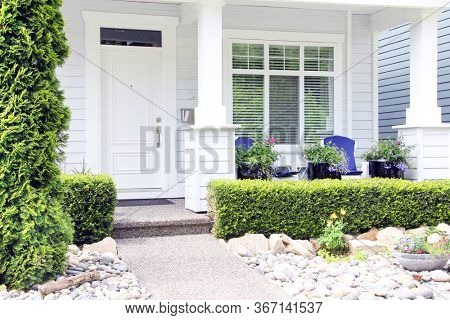 Beautiful brand new contemporary white home in a Canadian neighbourhood. Front door with a pretty porch and rock garden.