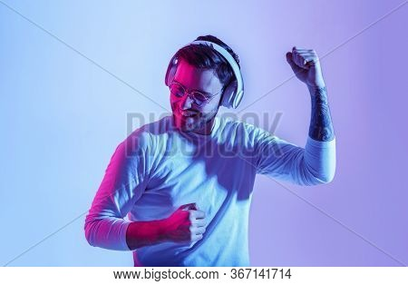 Dancing To Favorite Music. Fashionable Guy With Headphones Has Fun With Favorite Song, Studio Shot