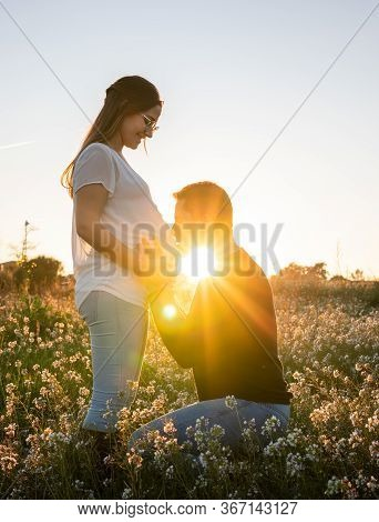 Young Pregnant Couple Man Kissing The Belly Into White Flowers Field With The Sunset And Sun Rays In