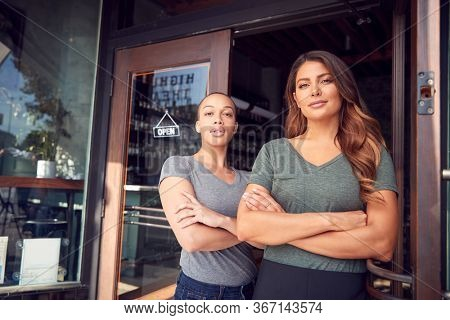 Portrait Of Two Women Starting New Coffee Shop Or Restaurant Business Standing In Doorway