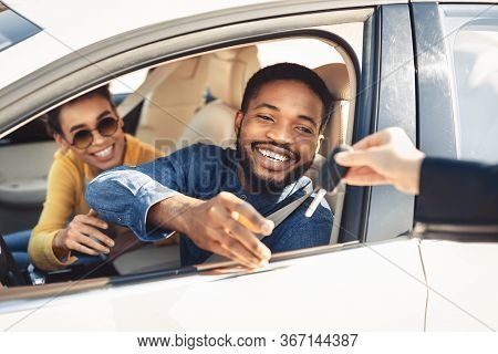 Buying Car. Happy African American Spouses Taking Key From Salesman For Test Drive Sitting In Automo