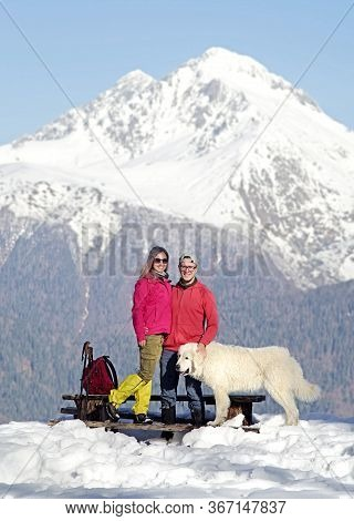 Happy Couple With Maremma Sheepdog In The Snow Mountains.