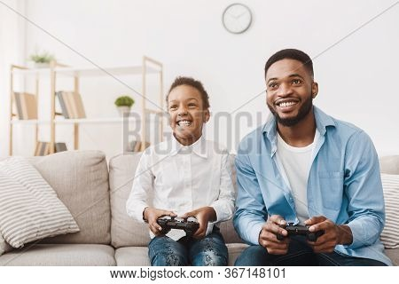Happy Afro Dad Enjoying Video Game With His Cute Daughter, Playing With Joysticks At Home, Free Spac