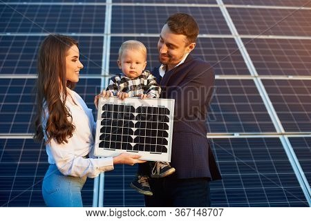 Young Happy Family On The Background Of Solar Panels. A Man, Woman And Child Are Holding A Solar Pan