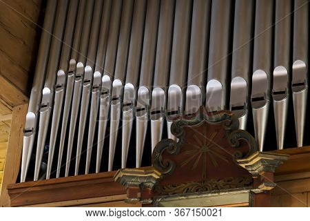 Pipe Organ In A Wooden Church Frontal Shot, Row Of Many Shiny Prospect Pipes Visible From Below, Clo