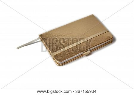 A Small Notebook In Gold Hardcover Color Isolated On A White Background. A Diary With A Bookmark Clo