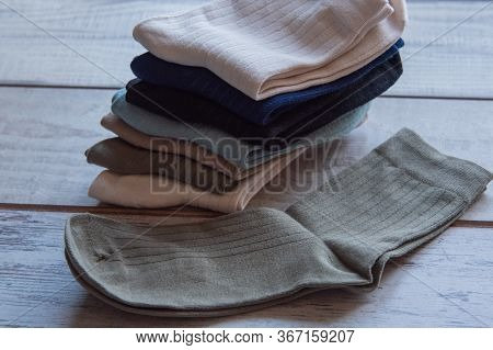 Socks Of Fine Jersey. View From Above. Many Socks On A Wooden Background. Socks Of Different Colors.