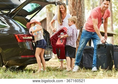 Family and children together at the suitcase packing at the car before the vacation trip