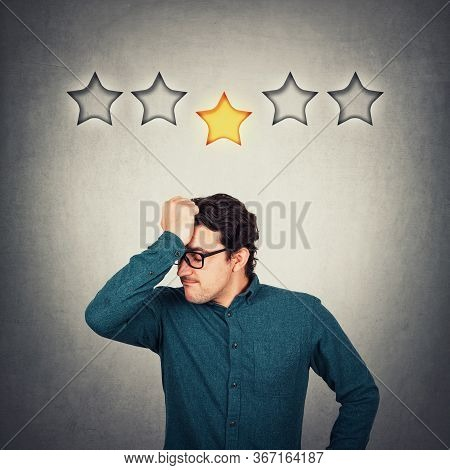 Annoyed Entrepreneur Keeps Hand To Forehead, Displeased Face Emotion, As Receives 1 Star Out Of 5 Fo
