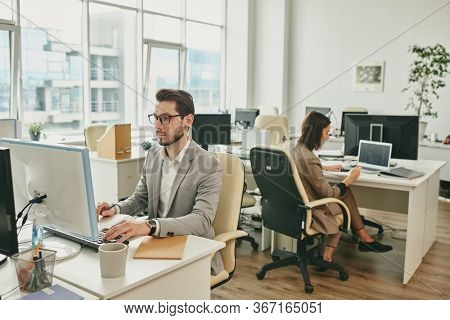 Two business people sitting at desks in office and using computers while their colleagues working from home during coronavirus isolation