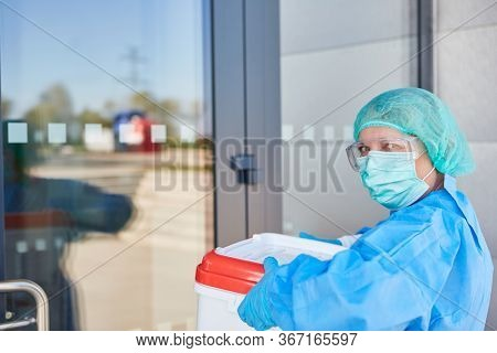 Doctor or surgeon with organ transport after organ donation for operation in front of the clinic entrance in protective clothing