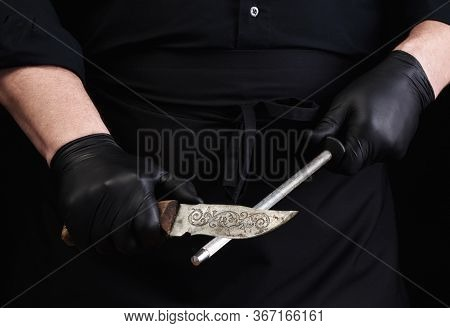 Chef In A Black Shirt And Black Latex Gloves Sharpen A Kitchen Knife On An Iron Sharpener With A Han