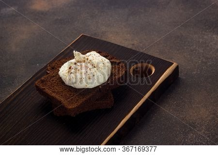 Healthy Breakfast Of Toast With Poached Egg, On A Dark Background And Chopping Board